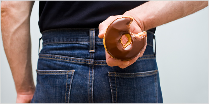 Man holding a half eaten Donut behind his back